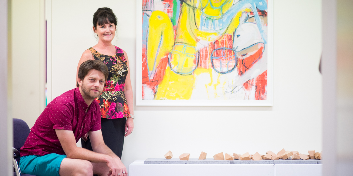 Carollyn Kavanagh and Tom Borgas alongside Borgas's Wooden Rocks and Stephen Langdon's acrylic painting Alice. Photo: Nat Rogers / InDaily