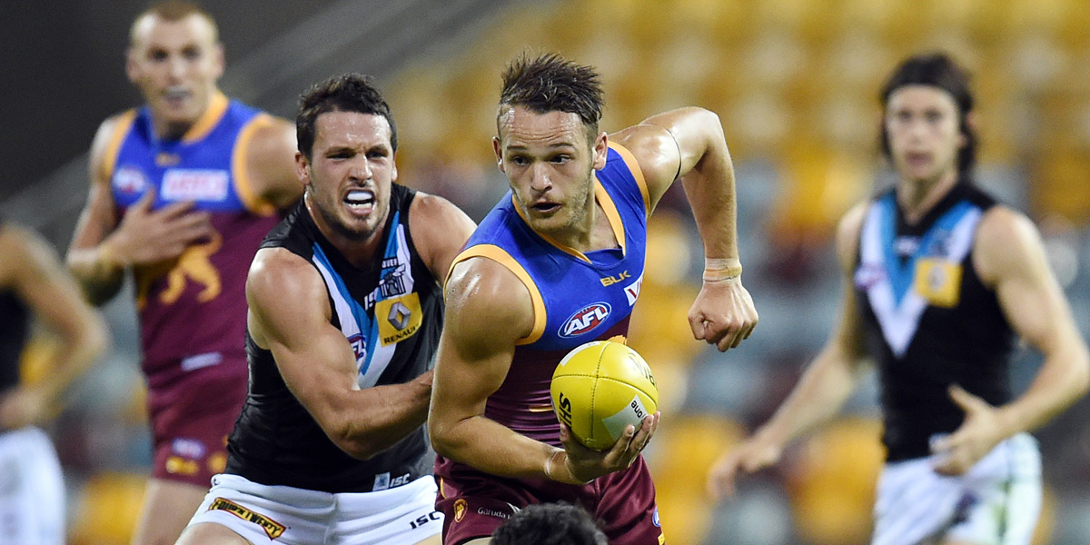 Brisbane's James Aish gets a handball away despite pressure from Port captain Travis Boak. AAP photo