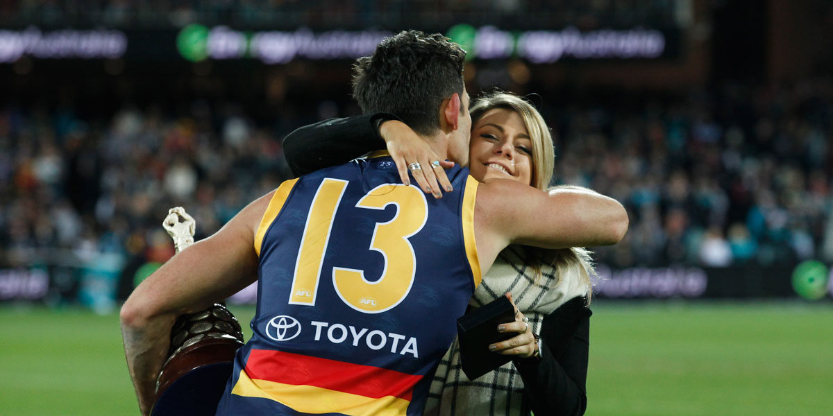 Crows captain Taylor Walker embraces Phil Walsh's daughter Quinn after the game. AAP image