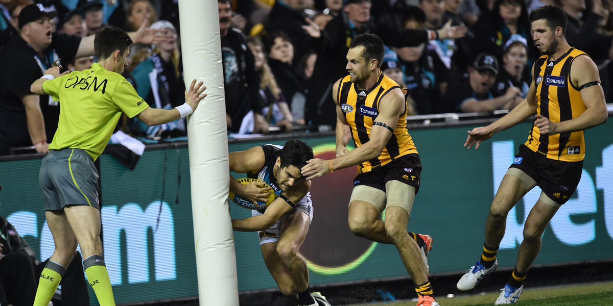 Luke Hodge and the goalpost create a Chad Wingard sandwich. AAP image