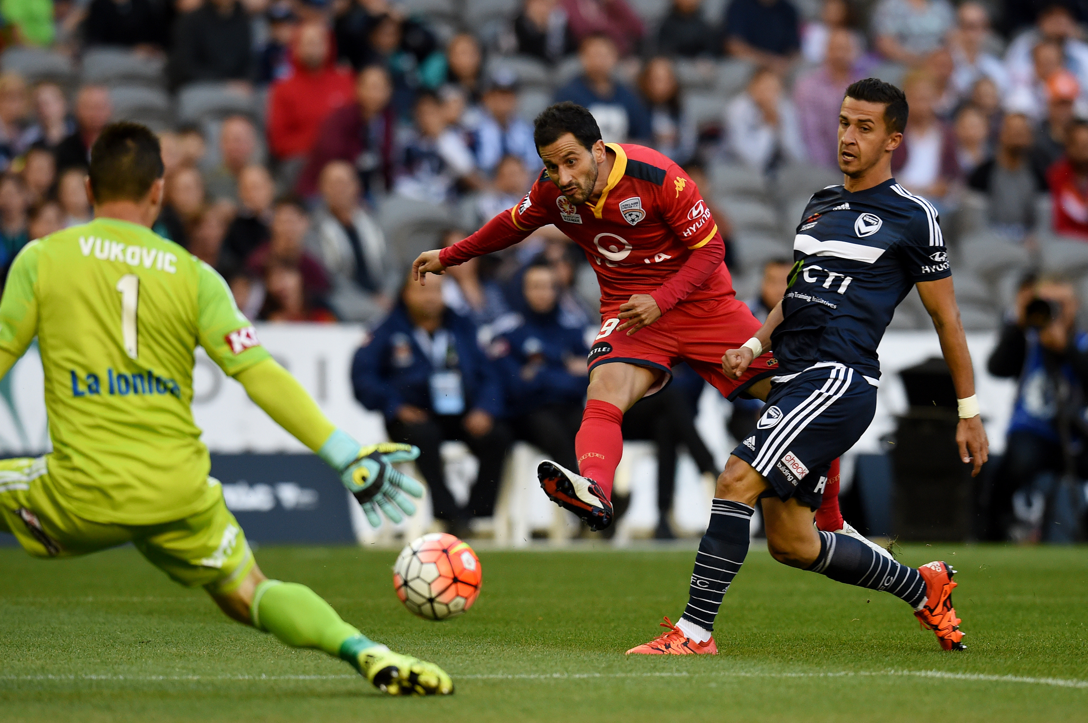 Sergio Cirio of Adelaide United tries to slip the ball past Victory 'keeper Daniel Vukovic. AAP Image/Tracey Nearmy