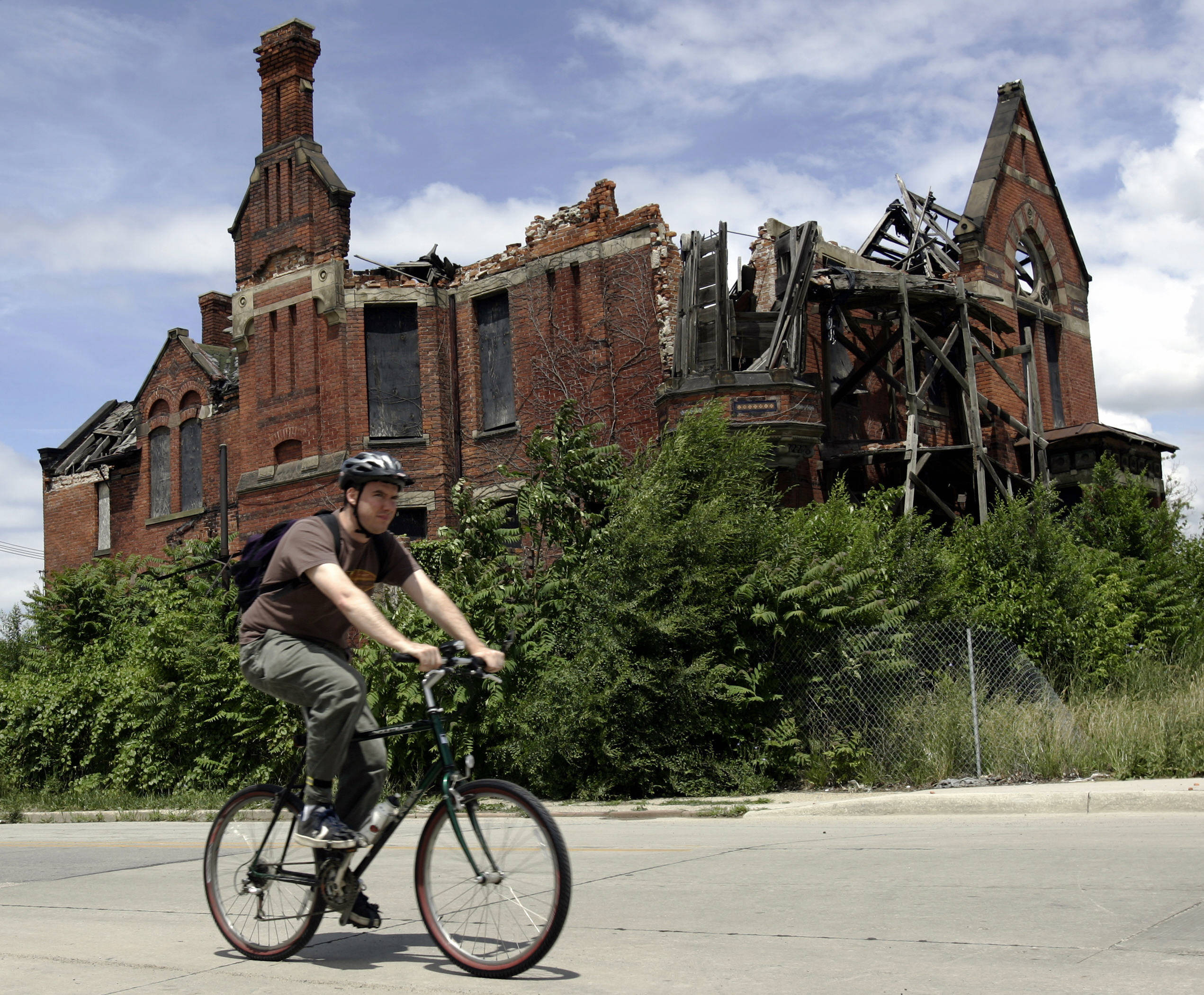 A resident passes an abandoned home in what was once a thriving middle class area in Detroit in 2005. AFP PHOTO/JEFF HAYNES
