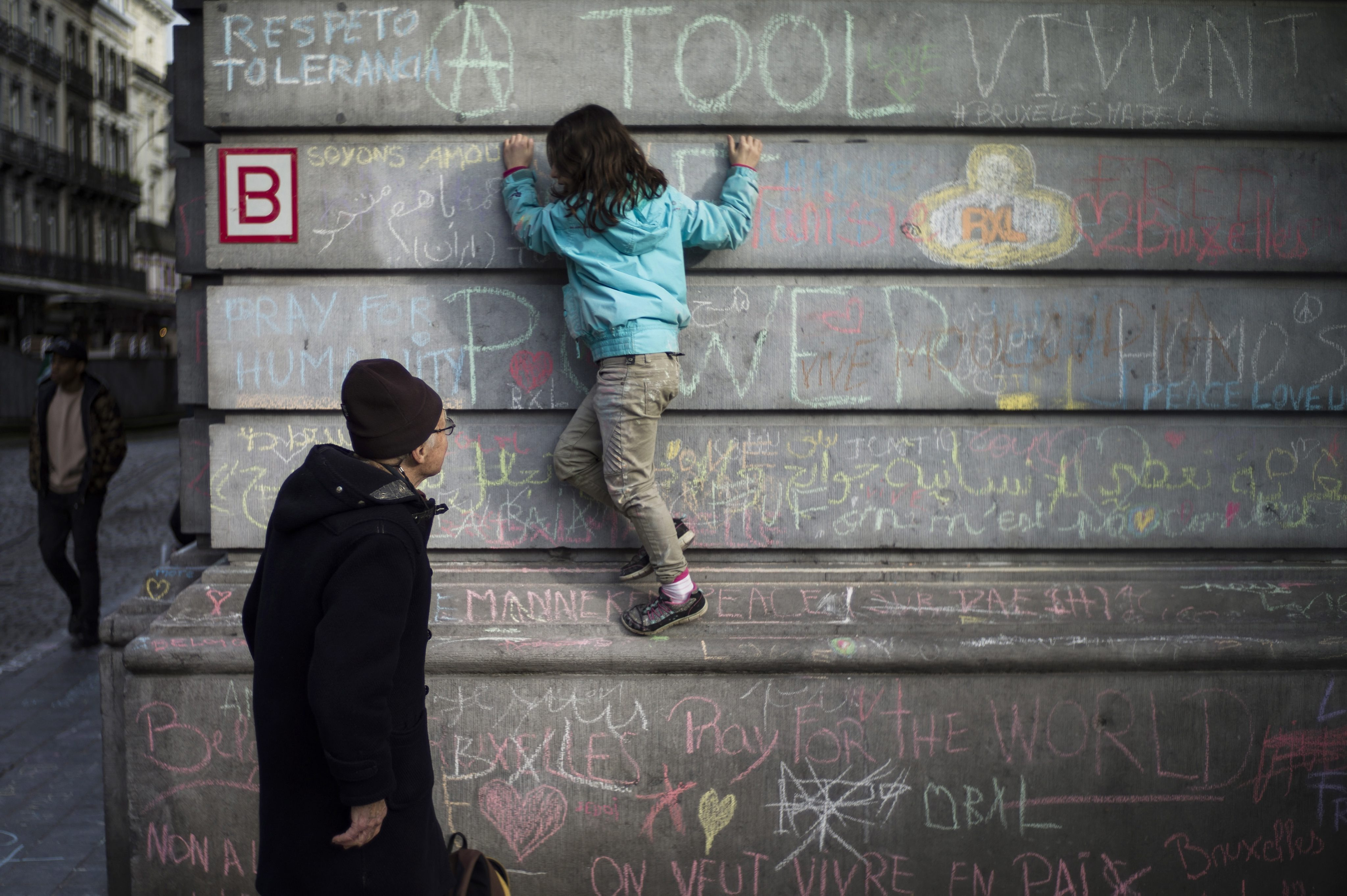 A little girl writes tribute messages on the wall at Place de la Bourse, Brussels. Photo: EPA/Yoan Valat