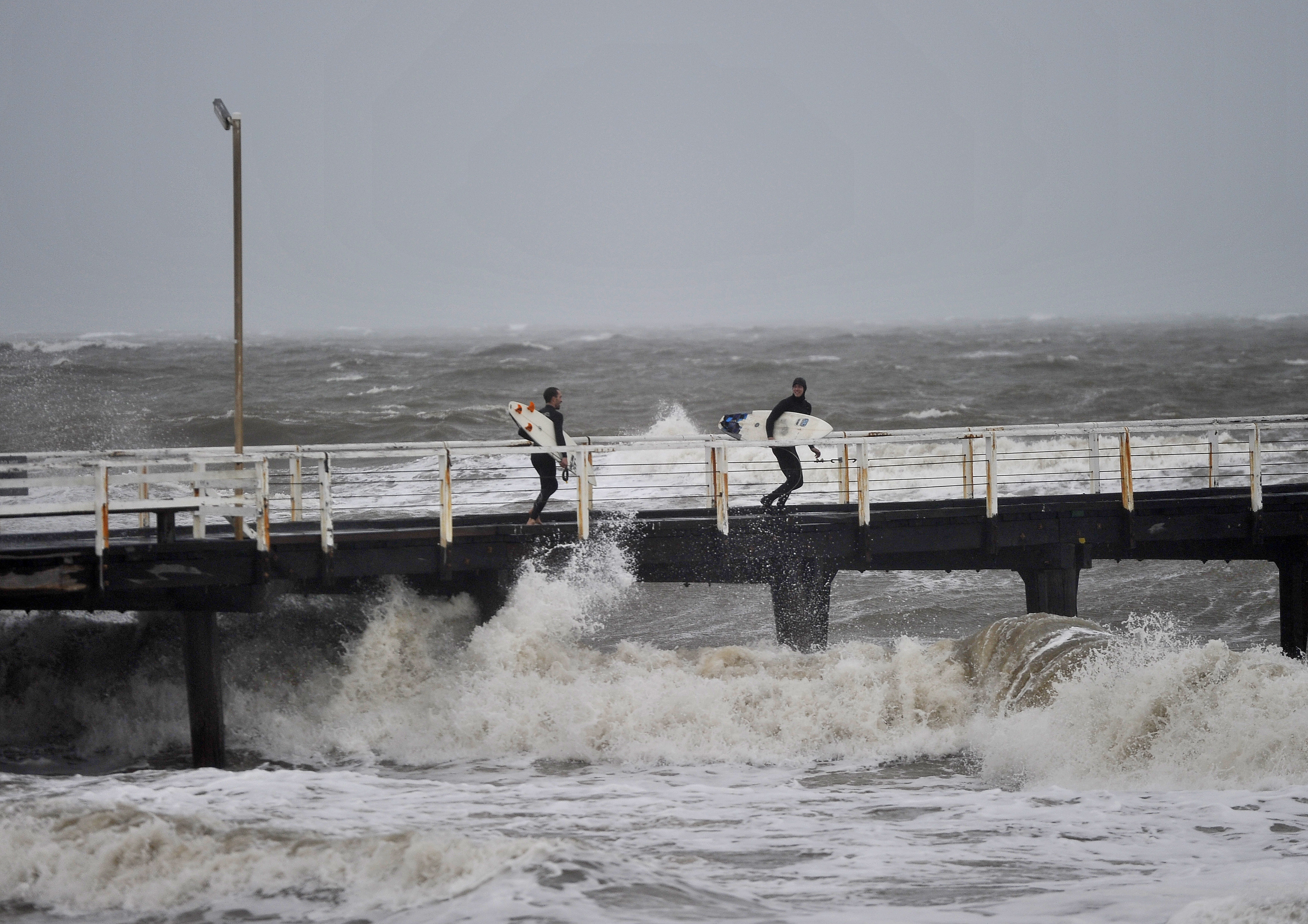 Surfers on a jetty look to jump into the waves that have been created by a storm front on Adelaide metropolitan beaches. Photo: AAP/David Mariuz