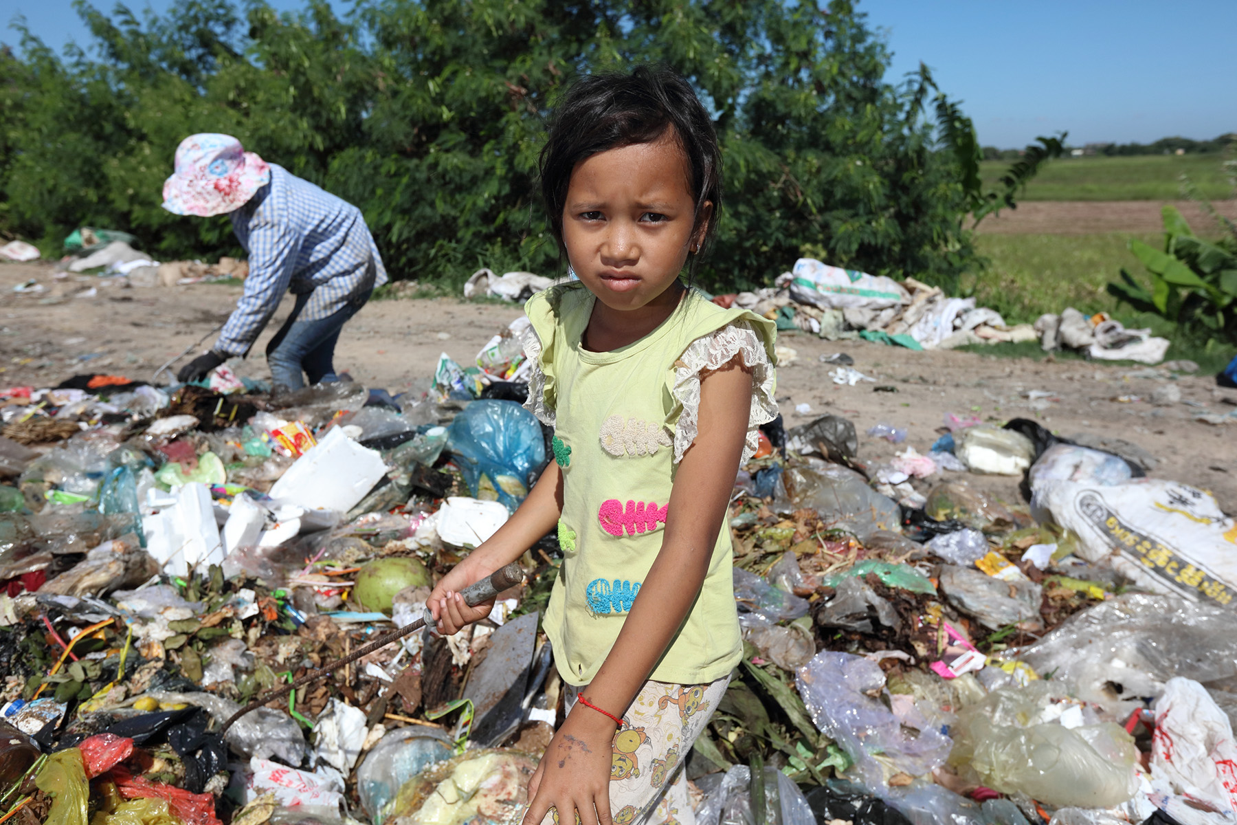 Sok Phear, 11 years old, scavenges through garbage at the rubbish tip in Takhmao looking for plastic to sell for 5c/ kilo.