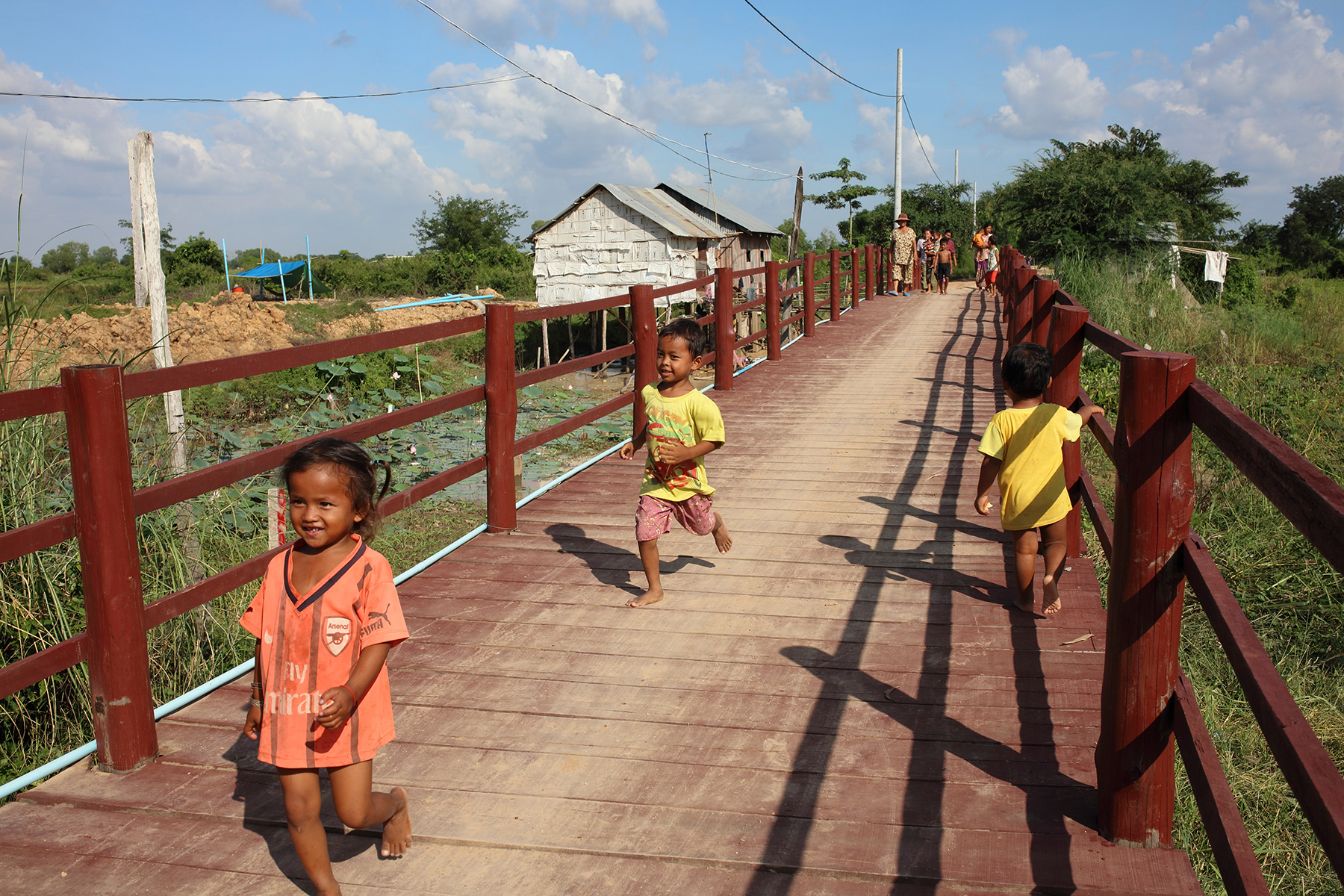 Children run across the bridge at Kom Nor Thmor village. The bridge was provided by Sunrise at a cost of $30,000; before it was built, during the rainy season children could not get to school. Photo: Tony Lewis