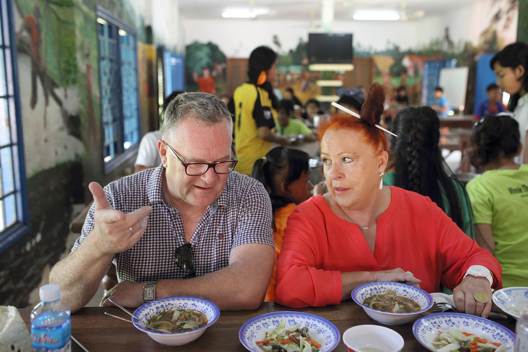 Kevin Tutt and Geraldine Cox eat lunch with the orphan children at Sunrise Kandal. Photo: Tony Lewis
