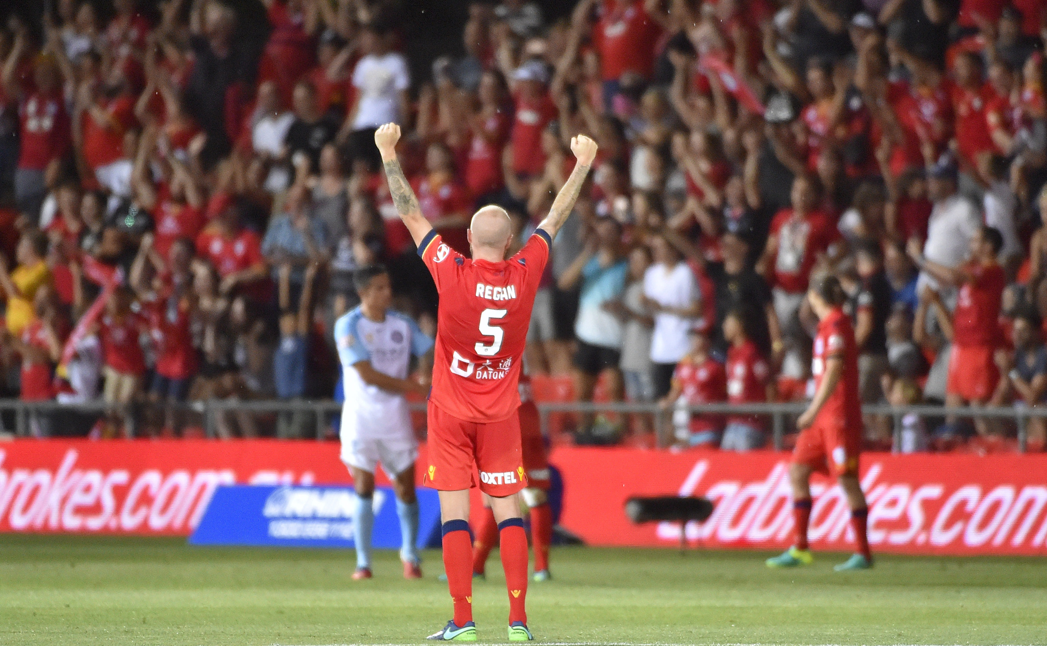 Taylor Regan raises his fists to the crowd after the Reds' breakthrough win against Melbourne City. Photo: David Mariuz / AAP