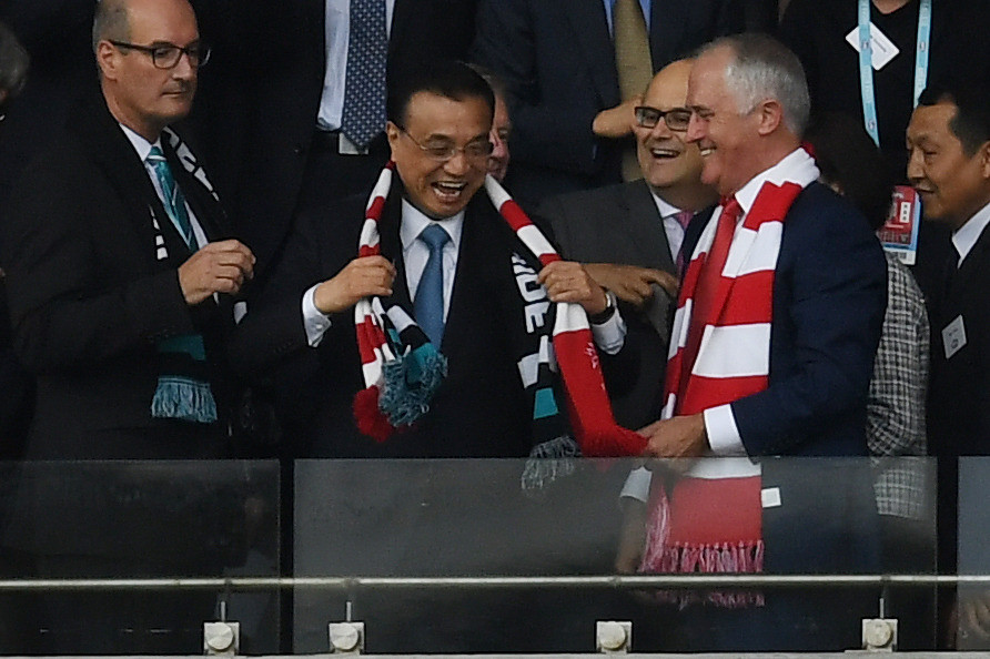 Chinese Premier Li Keqiang puts on a Swans scarf caught by Australian Prime Minister Malcolm Turnbull thrown up to him by a crowd member ahead of the Round 1 AFL match between the Sydney Swans and Port Adelaide at the Sydney Cricket Ground in Sydney, Saturday, March 25, 2017. (AAP Image/Dean Lewins) NO ARCHIVING, EDITORIAL USE ONLY