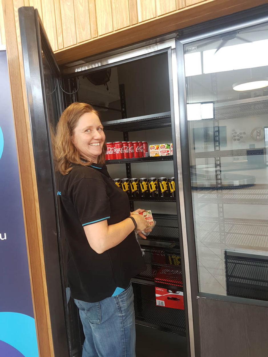 Mobo Group employee Bec Davis restocks the beverages. Bec, along with fellow employees Carmel and Julie, were instrumental in bringing the café to fruition.